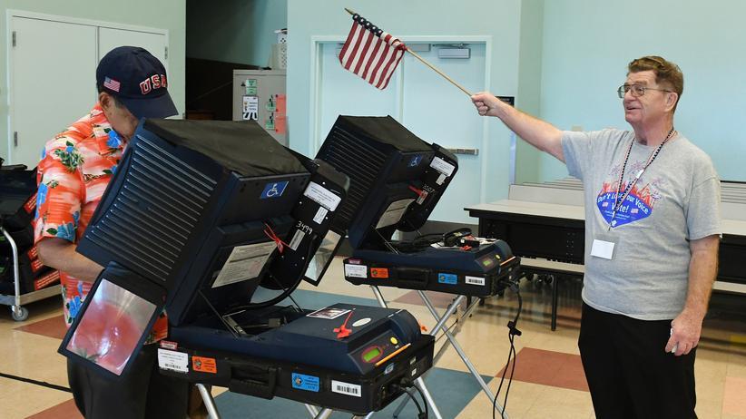 Cyberattacken: An einer Wahlstation in Las Vegas leitet ein Wahlhelfer die Wähler mithilfe einer US-amerikanischen Flagge zu den freien Wahlmaschinen.