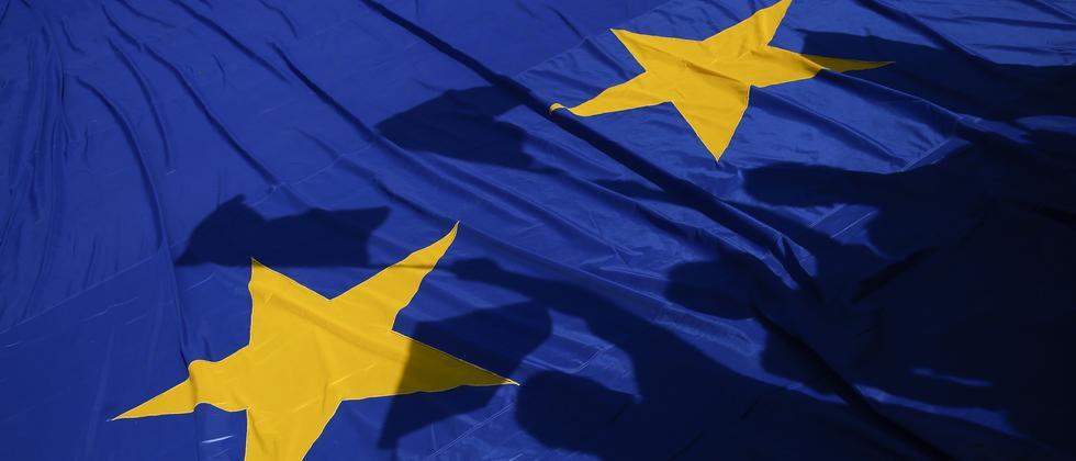Demonstranten verweisen in Rom auf die EU-Fahne.