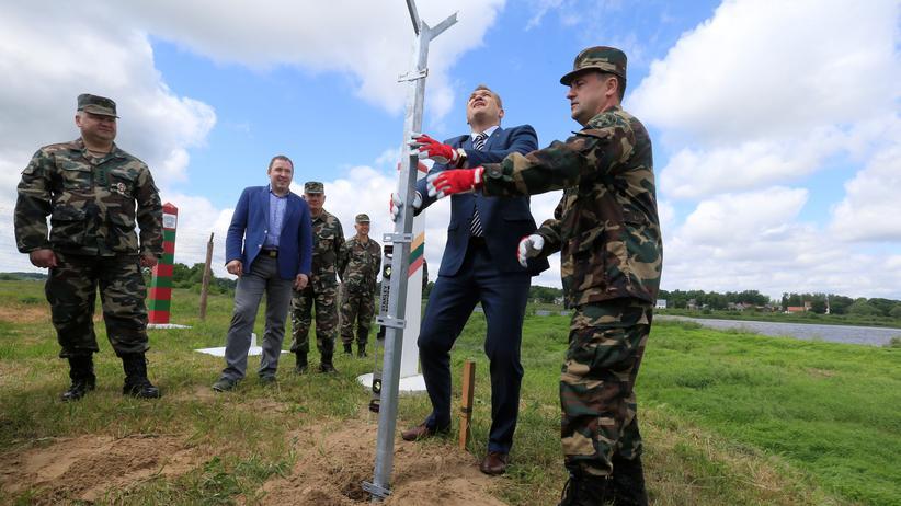 Europäische Union: Innenminister Eimutis Misiunas (2. v. r.) stellt mit Mitarbeitern der litauischen Grenzkontrolle den ersten Zaunpfahl auf.