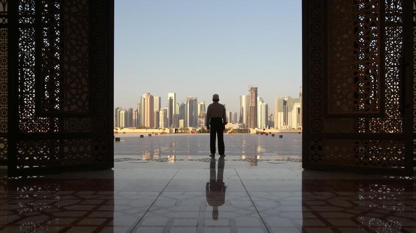 Katar-Krise: Ein Mann steht in einem Eingang der Imam-Muhammad-ibn-Abd-al-Wahhab-Moschee in Doha, Katar. Im Hintergrund ist die Skyline der Stadt zu sehen.