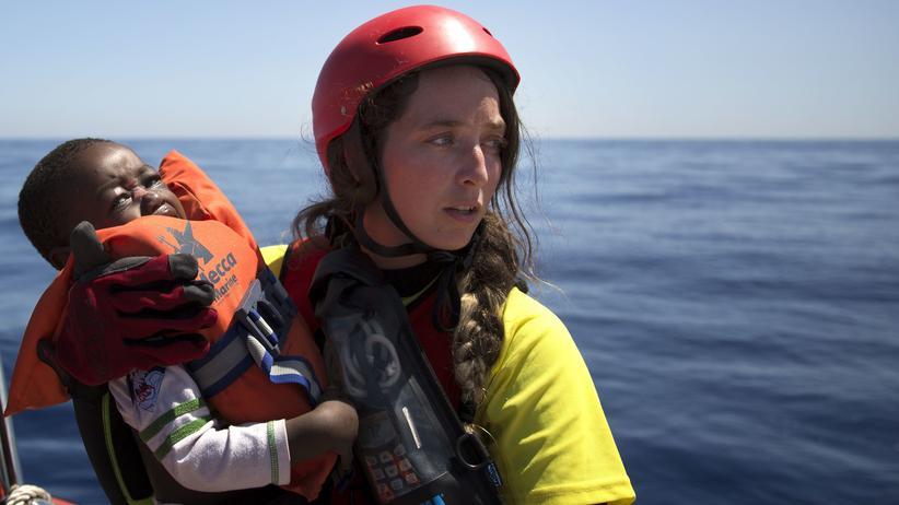 Mittelmeer: Eine freiwillige Helferin mit einem geretteten Kind, 18 Seemeilen vor der Libyschen Küste