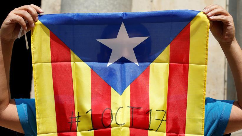 Spanien: Ein Unterstützer der katalanischen Unabhängigkeitsbewegung hält die katalanische Estelada-Flagge, auf der das Datum für das geplante Referendum steht.
