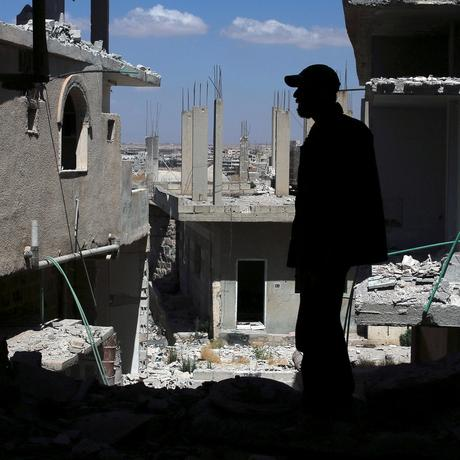 Ein Mann steht in einem vom Krieg zerstörten Haus im syrischen Deraa.