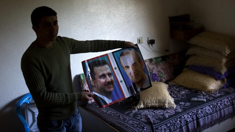 Syrien: Ein Syrer hält in seinem Haus ein Bild des Präsidenten Baschar al-Assad und dessen Vater Hafis al-Assad in die Höhe (Archiv, 2010).