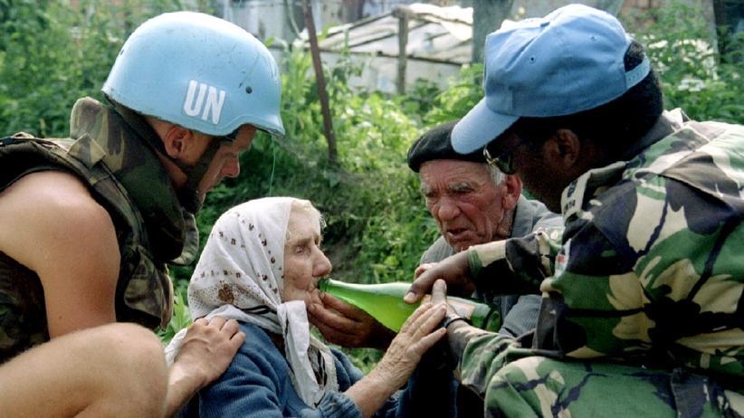 Den Haag: Ein niederländischer und ein kenianischer Blauhelmsoldat der UN versorgen am 13. Juli 1995 eine Frau in Potocari in Bosnien.