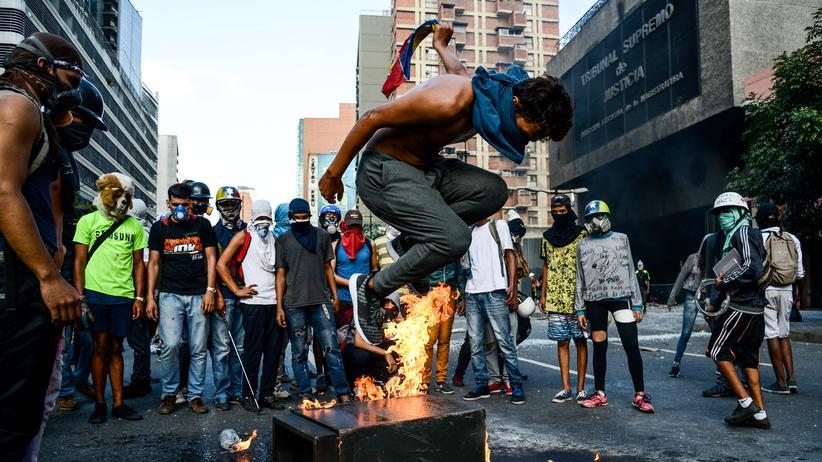 Demonstranten vor einem brennenden Gebäude des Obersten Gerichtshofes in Venezuela.