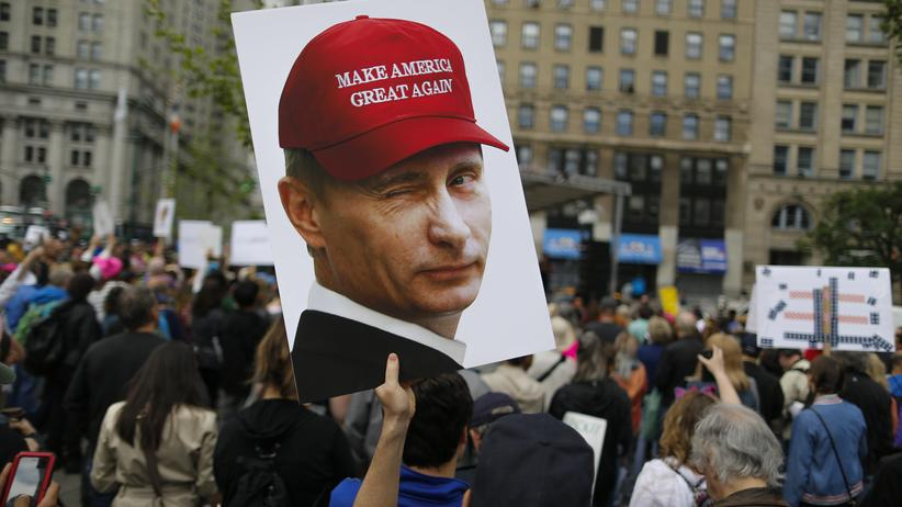 "Russland: Bei der Demonstration ""March for Truth"" in New York hält ein Teilnehmer ein Putin-Plakat hoch."