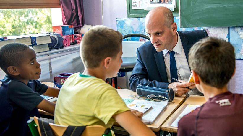 """Bildungsreform in Frankreich: Der französische Bildungsminister Jean-Michel Blanquer in einem Klassenzimmer mit Schülern – an dem Tag präsentierte er die Initiative """"Ein Buch für die Ferien""""."""
