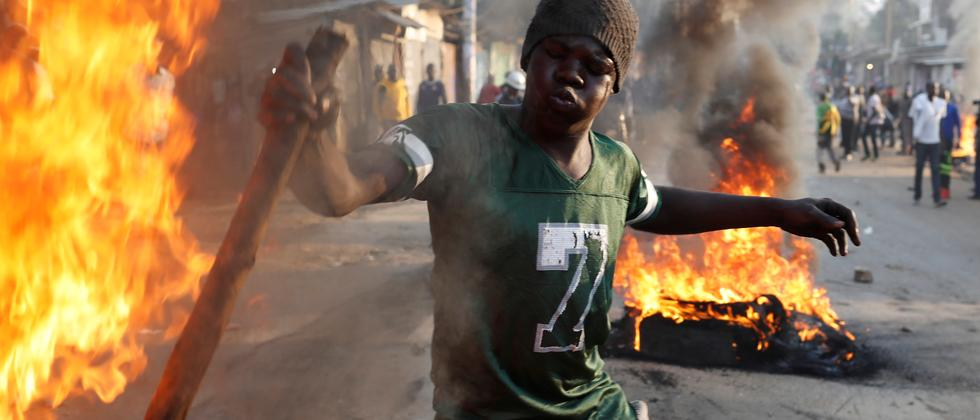 Ein Anhänger des Herausforderers Raila Odinga zündet einen Autoreifen an.