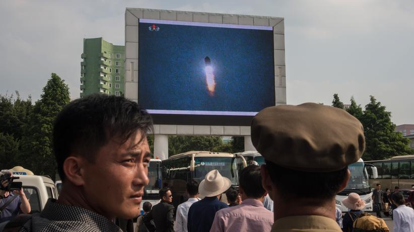 Raketentest: Nordkoreaner schauen die Berichterstattung über den Raketentest auf einem öffentlichen Platz in Pjöngjang.