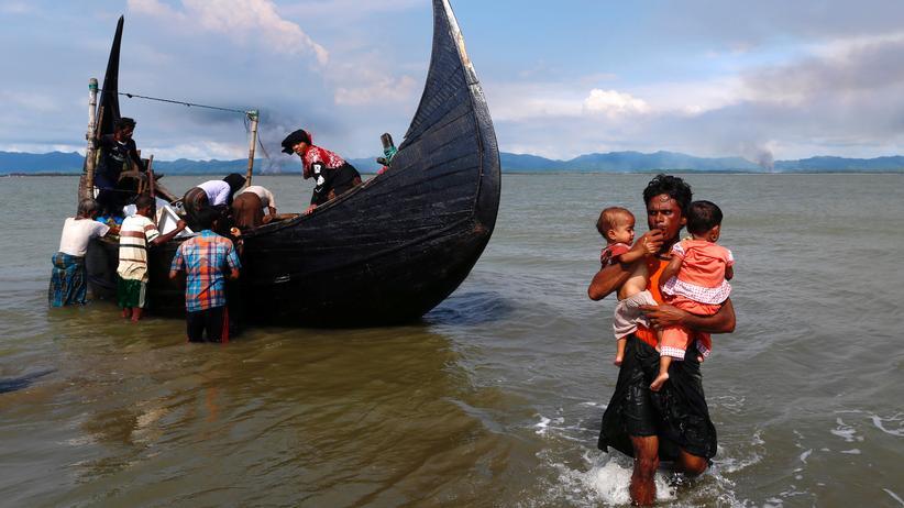 Bangladesch: Rauch steigt über Myanmar auf, während Rohingya-Flüchtlinge in Bangladesch an Land gehen.