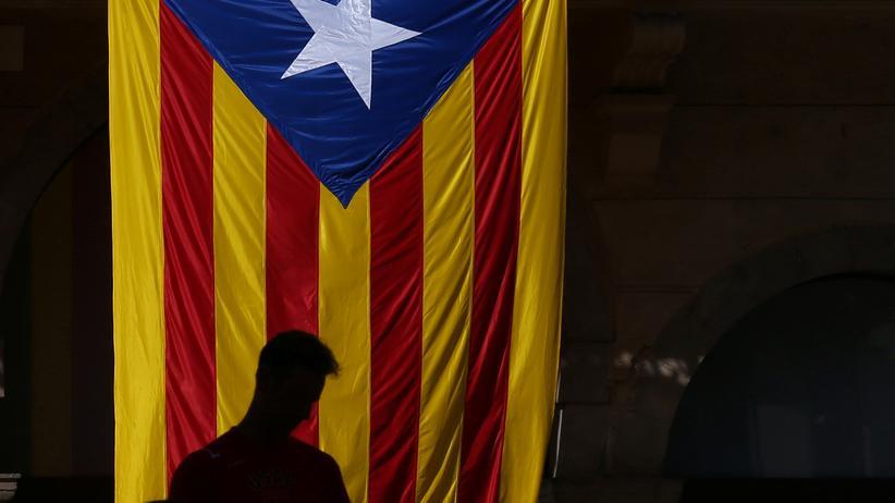 Spanien: Ein Mann steht vor der katalanischen Flagge.