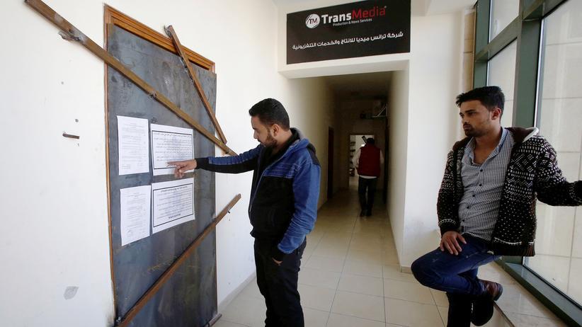 Nahostkonflikt: Palästinenser stehen vor dem Eingang der Firma Transmedia, die von der israelischen Armee geschlossen wurde.