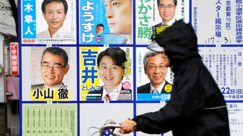 Neuwahl: Kurz vor der Wahl in Tokyo: Eine Frau in Regenkleidung radelt an Wahlplakaten vorbei.