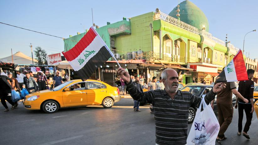 Kirkuk: Nachdem Bagdad hier wieder die Kontrolle hat: Ein Straßenverkäufer bietet auf der Hauptstraße von Kirkuk irakische Nationalflaggen an.