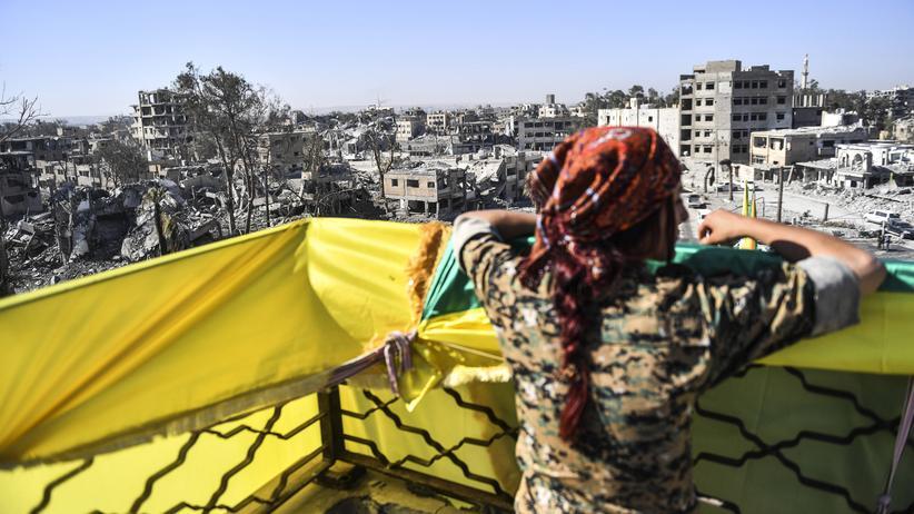 """""""Islamischer Staat"""": Eine Kämpferin der Syrian Democratic Forces blickt von oben auf den Al-Naeem-Platz in Rakka, wo die Vertreibung der Dschihadisten gefeiert wird."""