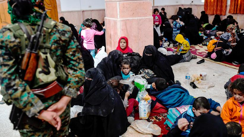 Syrien: Eine Kämpferin der Syrischen Demokratischen Kräfte steht zwischen Zivilisten, die aus dem Zentrum der syrischen Stadt Rakka geflüchtet sind.