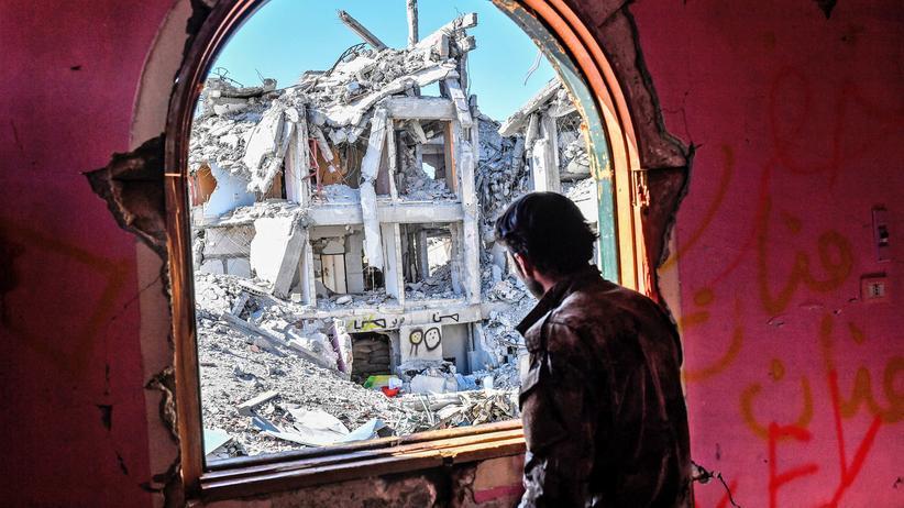 Syrien-Gipfel: Ein Kämpfer der Demokratischen Kräfte Syriens vor Trümmern in der syrischen Stadt Rakka