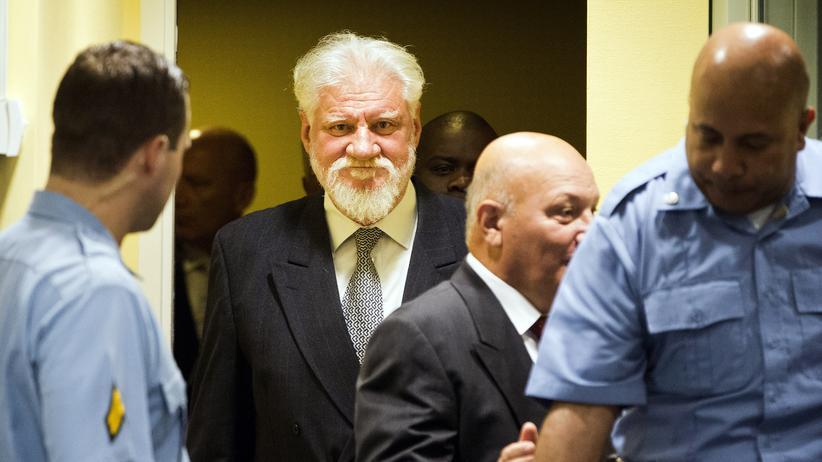 Slobodan Praljak: Der ehemalige Kommandeur Slobodan Praljak (Mitte) betritt den Gerichtssaal in Den Haag.