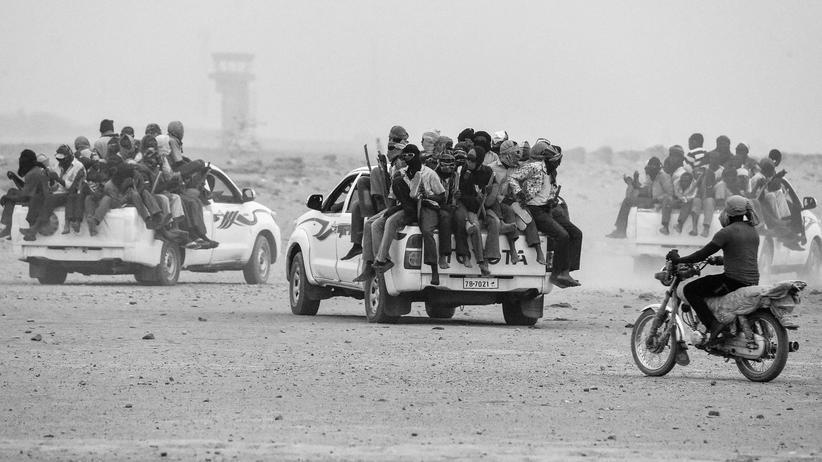 Flüchtlinge: Flüchtlinge verlassen das nigrische Agadez Richtung Libyen. Viele haben Stöcke an der Ladenfläche des Pick-ups verkeilt oder angebunden, um während der Fahrt nicht vom Wagen zu stürzen.