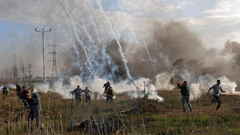 """""""Tag des Zorns"""": Palästinenser schützen sich vor Tränengas, hier an der Grenze des Gazastreifens zu Israel."""