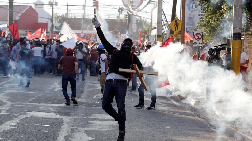 Honduras: Ein Demonstrant wirft in Tegucigalpa einen Tränengasbehälter zurück zu den Polizisten.
