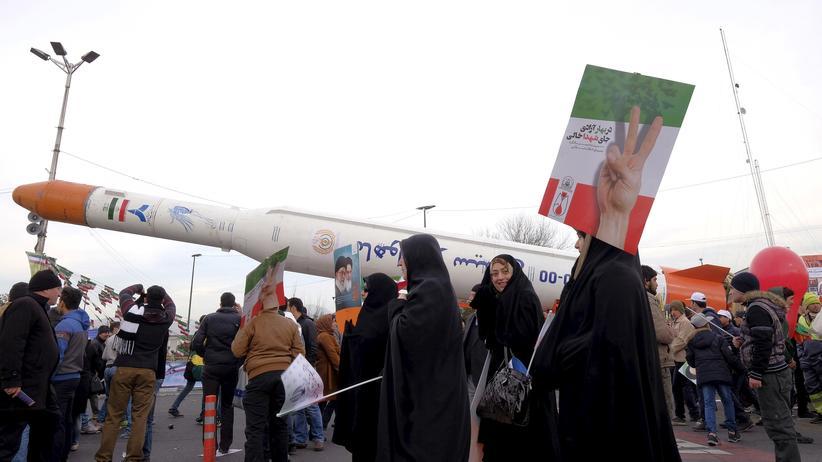 Iran: Menschen stehen während einer Jubiläumsfeier zur Islamischen Revolution um das Modell einer Rakete (Archiv).