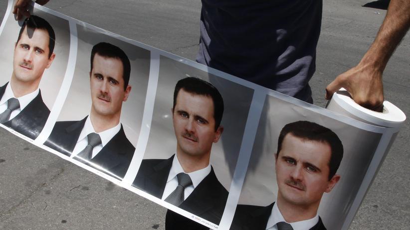 Syrien: Ein Assad-Anhänger rollt zu Beginn des Bürgerkrieges 2011 eine Banderole mit dem Bild des Machthabers in Damaskus aus.