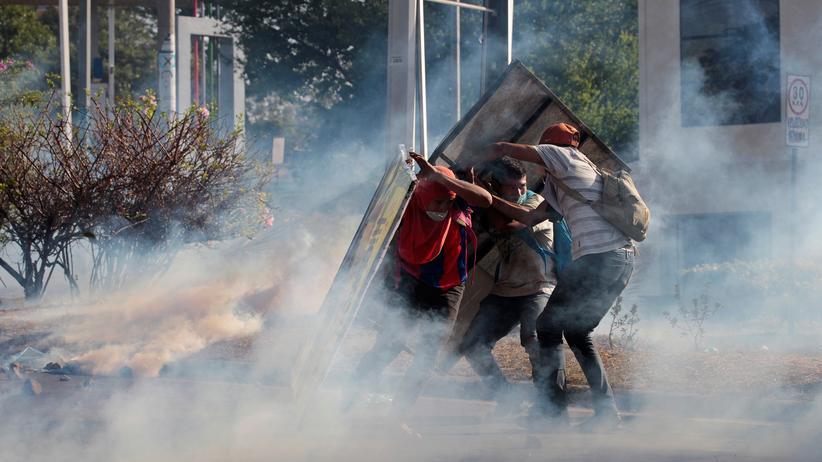 Nicaragua: Managua am Freitagabend: Demonstranten schützen sich vor Tränengas.