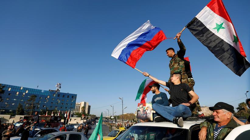 Syrien: Syrer mit den Flaggen Russlands und Syriens in Damaskus