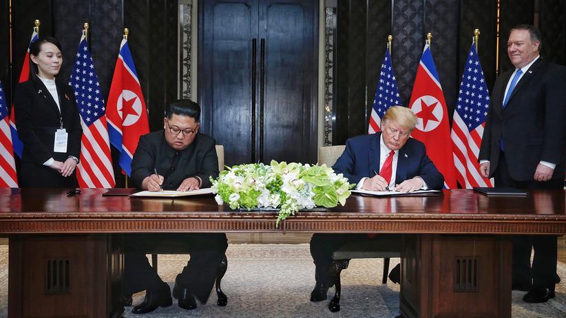 USA und Nordkorea: Nordkoreas Machthaber Kim Jong Un und der US-Präsident Donald Trump setzen ihre Unterschrift unter eine gemeinsame Gipfelerklärung.