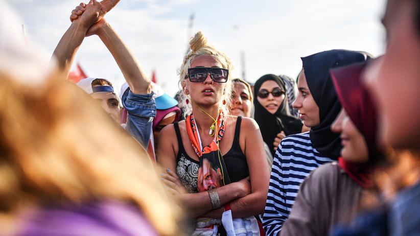 Türkei: Eine junge Frau hört der Wahlkampfrede von Recep Tayyip Erdoğan am Yenikapı-Platz in Istanbul zu.