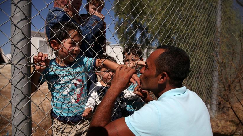EU-Asylpolitik: Ein Mann küsst seine Kinder, die in einem Flüchtlinscamp auf Zypern angekommen sind