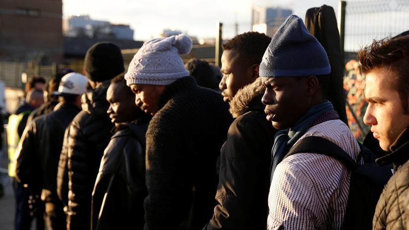 Flüchtlingspolitik: Flüchtlinge warten an einer Essensausgabe nahe einem Flüchtlingszentrum am Porte de la Chapelle in Paris.
