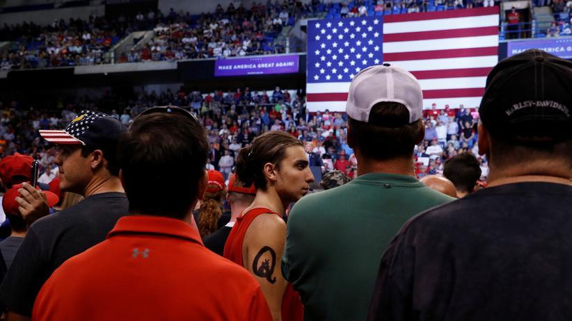 QAnon: Ein Anhänger der QAnon-Verschwörungstheorie mit entsprechendem Logo auf dem Arm (Mitte) bei einer Kundgebung von Donald Trump im US-Bundesstaat Pennsylvania, August 2018.