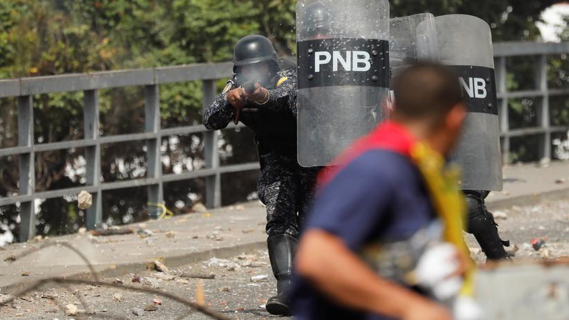Venezuela: Caracas: Ein Polizist schießt mit Gummigeschossen auf Demonstranten.