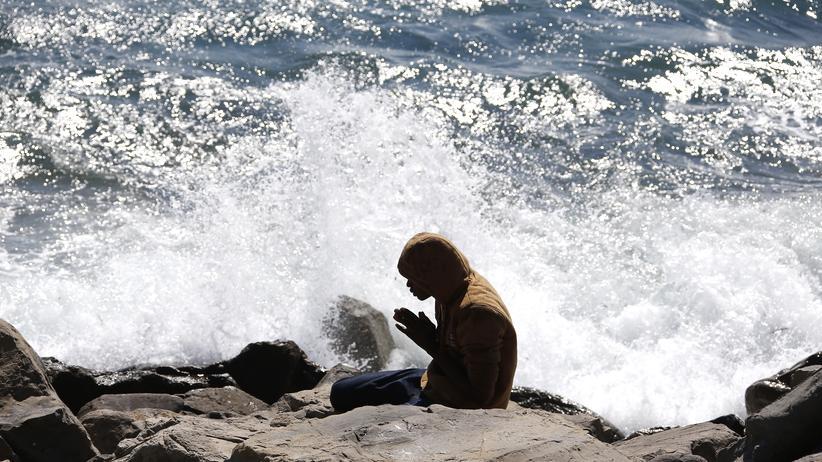 Italien und Frankreich: Ein Flüchtling betet an der französisch-italienischen Küste.