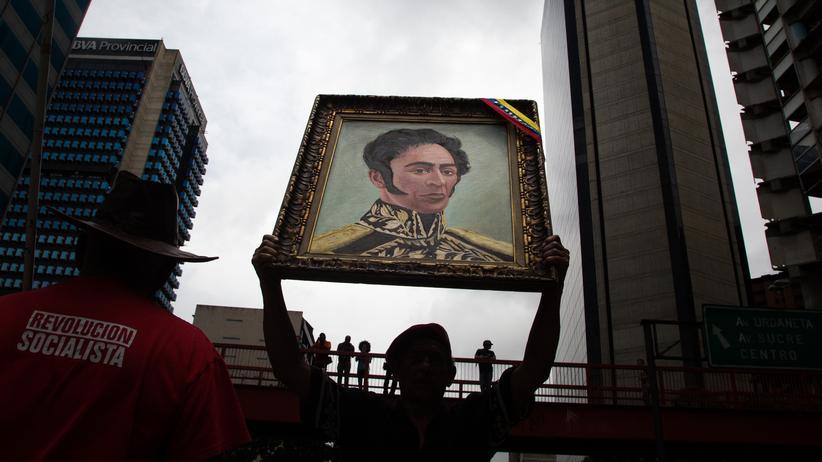 Lateinamerika und die USA: Ein Unterstützer des venezolanischen Staatschefs Nicolás Maduro mit einem Bild des Freiheitskämpfers Simón Bolívar