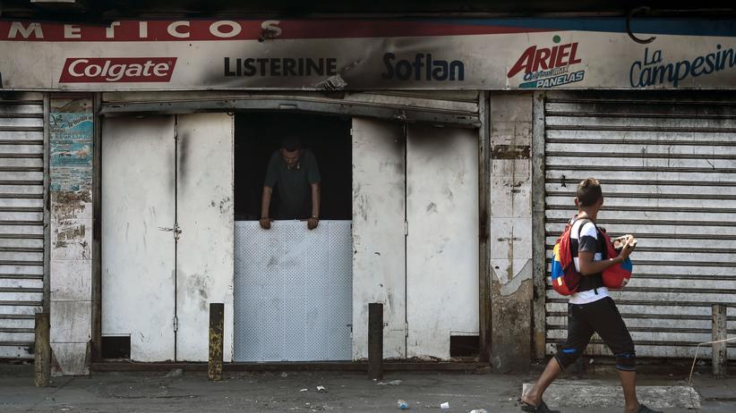 Nicolás Maduro: Ein Passant vor einem der vielen geplünderten Läden in Maracaibo