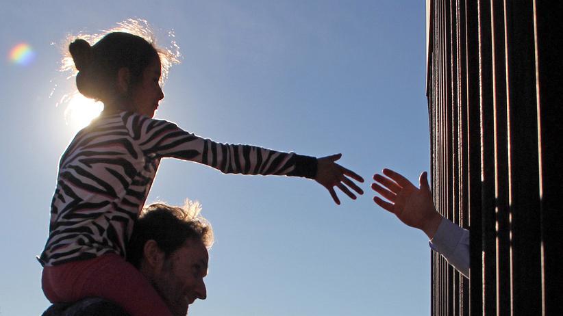 US-Republikaner: Ein Mädchen fasst von der Seite der mexikanischen Stadt Ciudad Juárez durch den Zaun eine Hand aus den USA.