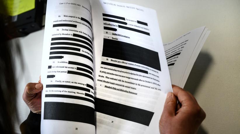 Mueller-Bericht: Ein Journalist liest den mit Spannung erwarteten Mueller-Bericht. Passagen, die auf Quellen oder Ermittlungsmethoden hinweisen, wurden geschwärzt.