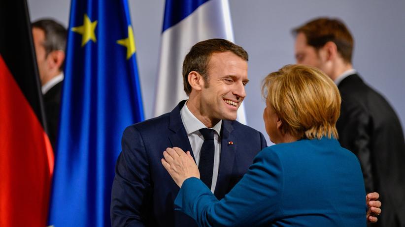 Angela Merkel: Angela Merkel und Emmanuel Macron begrüßen sich in Aachen, wo sie Mitte Januar mit einem neuen Abkommen den deutsch-französischen Freundschaftsvertrag erneuerten.