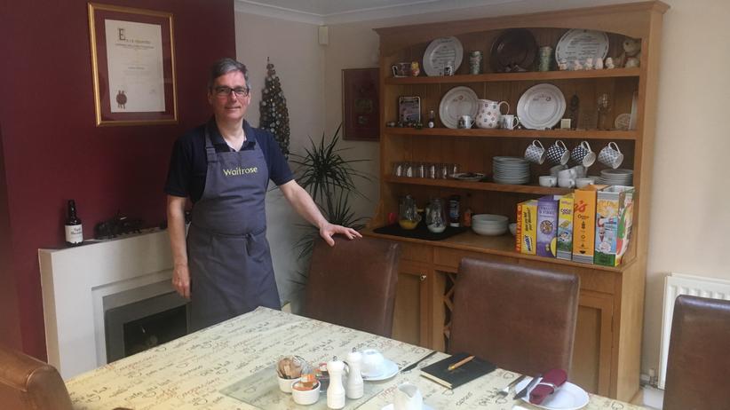 Laurent steht vor dem Esstisch, an dem sich Jane, Richard und Michael für das Brexit-Dinner zur Debatte getroffen haben.