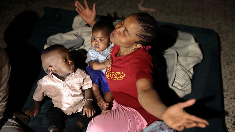 UN-Flüchtlingshilfswerk: Eine Frau mit zwei Kindern in einem Flüchtlingsheim nahe Tripolis: Die Unterkunft wurde Anfang Mai von einem Schrapnell getroffen und teilweise zerstört.