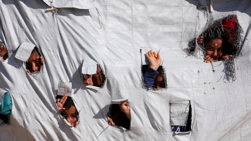 Syrien: Kinder gucken in einem syrischen Flüchtlingslager aus einem Zelt.