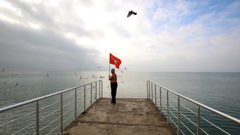Ukraine-Konflikt: Ein Mann mit einer sowjetischen Fahne am Strand der Schwarzmeerinsel Krim