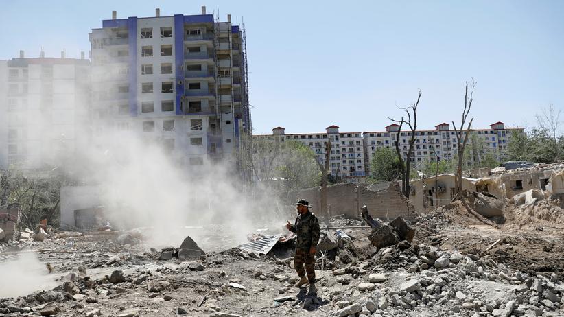 Dialogkonferenz: Ein Soldat steht nach einem Bombenangriff am Anschlagsort: Die Gewalt in Afghanistan soll reduziert werden.