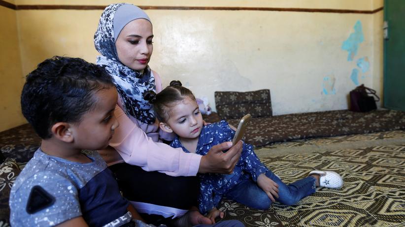 Flüchtlinge: Eine syrische Frau spricht mit ihrem Mann in Deutschland.