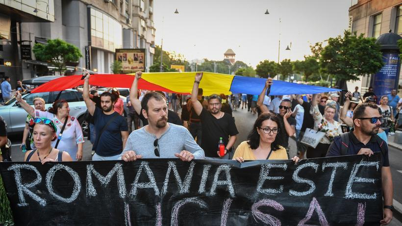 """Rumänien: Bei einer Demonstration in Bukarest halten Teilnehmende ein Banner mit der Aufschrift """"Rumänien ist getötet"""" hoch, um an den Mord an einer 15-Jährigen zu erinnern."""