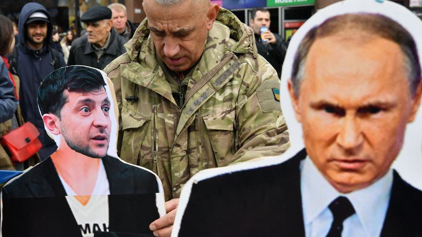 Russland: Vor der Präsidentschaftswahl in der Ukraine im März stellt ein Aktivist Kartonaufsteller von Wolodymyr Selenskyi (links) und dem russischen Staatschef Wladimir Putin auf.